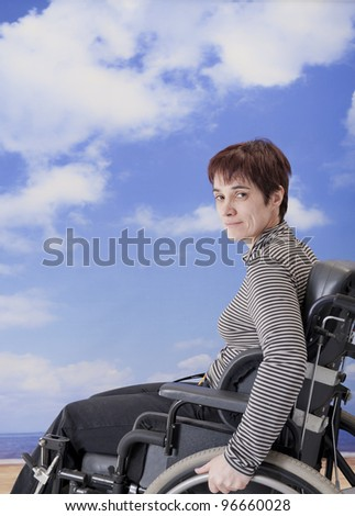 handicapped woman in wheelchair at the beach