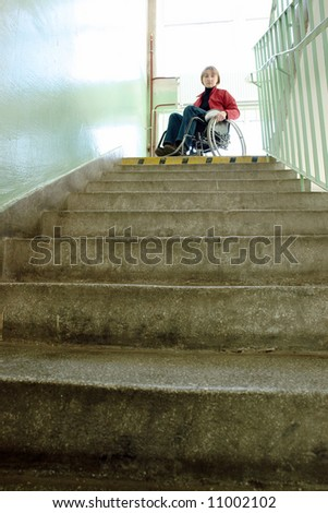 Handicapped woman on wheelchair looking down the stairs in building staircase - stock photo
