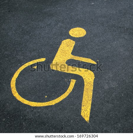 Handicapped yellow symbol on asphalt. - stock photo