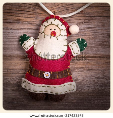 Handicraft Christmas decoration, felt Santa Claus, over old wood background.  Filtered to look like an aged instant photo. - stock photo