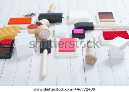 handicraft equipments, ink pads, lino cutter, paint roller and plasticine blocks on white wood table - stock photo
