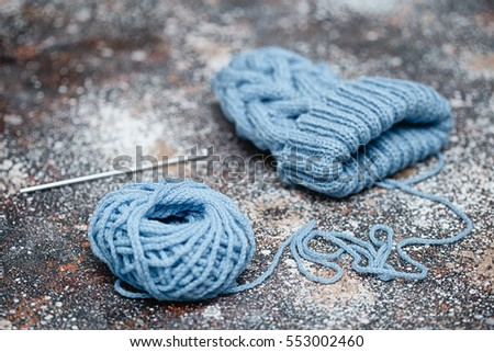 handicraft, love, valentines day and needlework concept - hand-knitted item with knitting needles and thread in heart shape