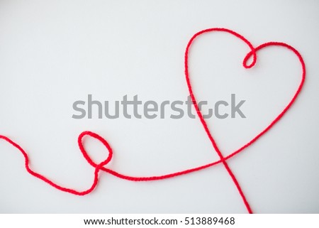 handicraft, love, valentines day, healthcare and needlework concept - red knitting yarn thread in shape of heart