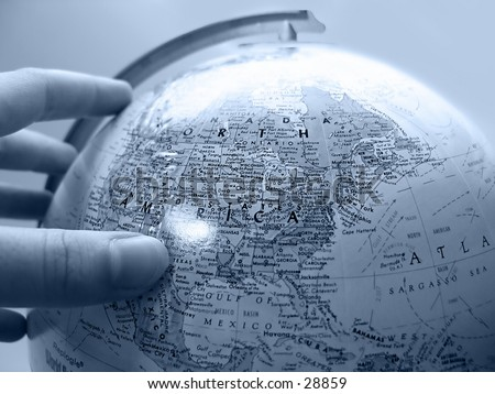 Handing about to turn the globe on its axis. Light blue tones. - stock photo