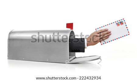 Handing an envelope with US stamp in a mailbox - stock photo