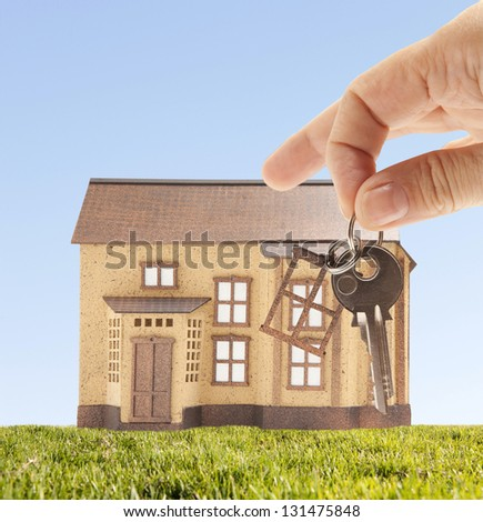 Handing keys in the house sky background - stock photo