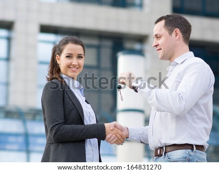 handing keys over in front of house - stock photo