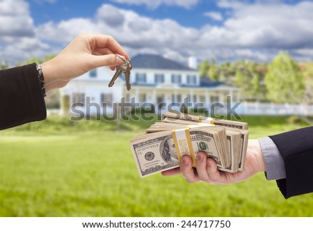 Handing Over Cash For House Keys in Front of Beautiful New Home. - stock photo