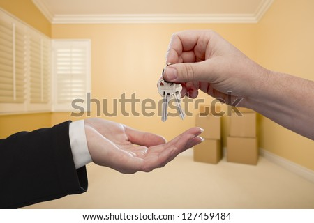 Handing Over the House Keys To A New Home Inside Empty Room. - stock photo