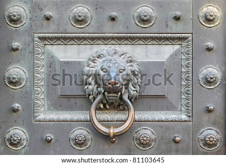 Handle antique bronze door in the form of head of a lion on a ring - stock photo