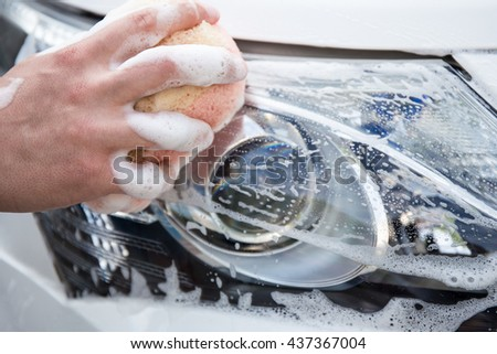 handle carwash concept - male hand washing car headlamp with sponge and foam - stock photo