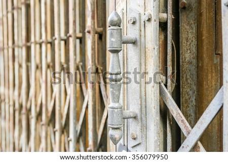 Handle door of old rusty metallic or steel or iron door. - stock photo