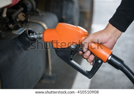 Handle fuel nozzle to refuel. Vehicle fueling facility.