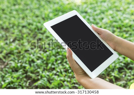 Handle the tablet,Side view of a woman's hand holding a modern tablet - stock photo
