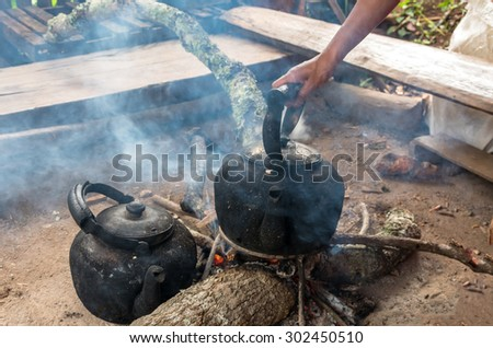 Handle Vintage traditional kettle for boiling water on Wood sticks - stock photo