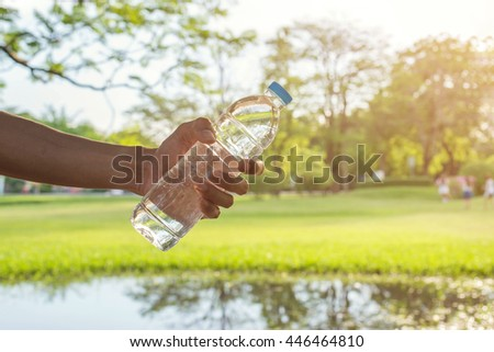 Handle water bottle on nature background