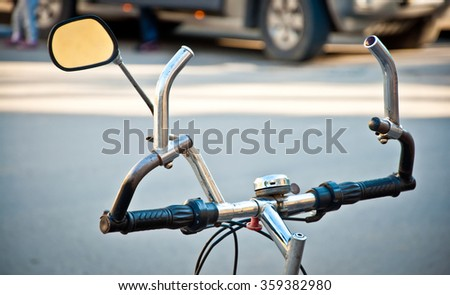Handlebar of retro bicycle with mirror which is standing on the street