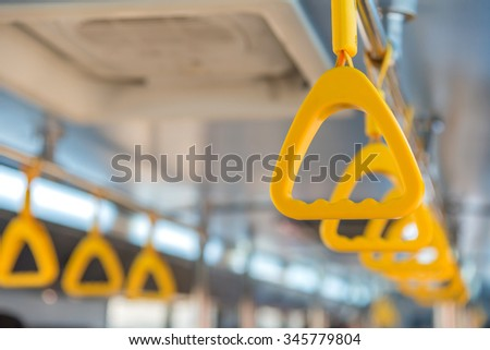 Handles on ceiling for standing passenger inside a bus. - stock photo