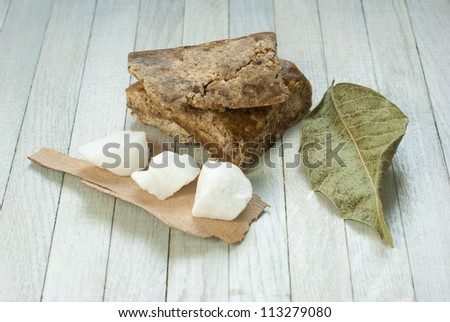 handmade african black soap and ingredients, dried  leaves and white shea butter - stock photo