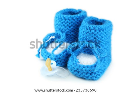 Handmade baby booties with pacifier isolated on a white - stock photo