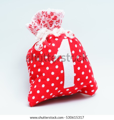 Handmade bag with a gift to the first number. From red fabric cloth with white polka dots, lace complication. One inscription. On seamless white background.
