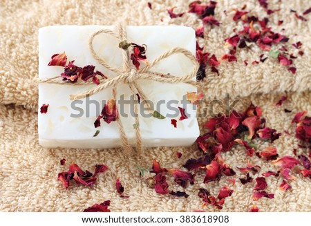 Handmade bar of soap with herbal rose petals, beige terry bath towel. - stock photo