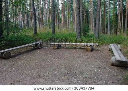 Handmade benches in the woods. Design of space for relaxation on outside. Benches for resting natural from trees and logs surrounding nature. Relax in the yard. Harmony and unity with nature. - stock photo