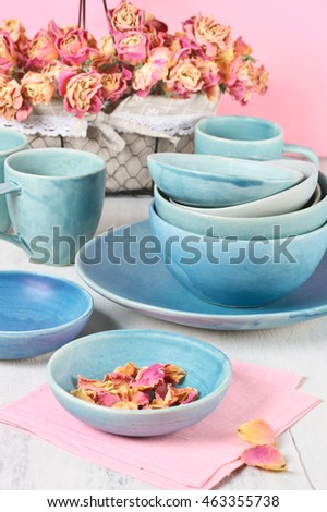 Handmade blue ceramic dishware set and wire basket with dried roses on rustic white wooden table against pink wall.