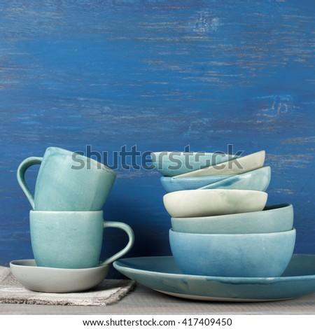 Handmade blue crockery set against rustic blue painted wall. - stock photo
