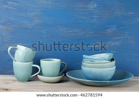 Handmade blue crockery set against rustic blue painted wall.