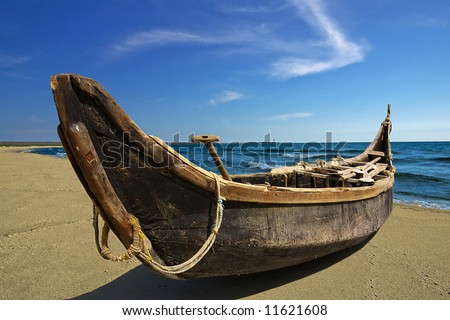 Handmade-boat on seacoast on a background of the blue sky with a cloud in the form of an arrow. - stock photo