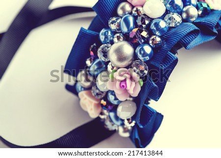 Handmade bracelet with different jewels on white background. Not isolated. Vintage - stock photo