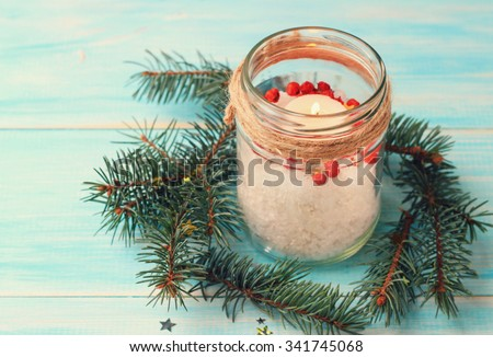 Handmade candle decor. Candle in glass jar, pine boughs, epsom salt, twine. Wooden blue background. Toned. - stock photo