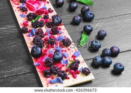 Handmade chocolate bars white, Ingredients for white chocolate blackberries, blueberries, blueberry, raspberry, candied violet petals, mint leaves, candy heart on dark black background wooden surface