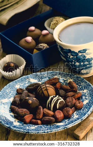 Handmade chocolate candies with cup of tea, cocoa beans, blue gift box on the vintage wooden table, toned - stock photo