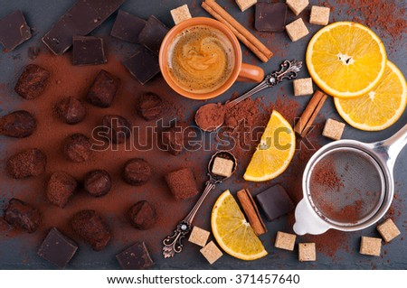 Handmade chocolate truffles with orange and cinnamon. Candies, chocolate, citrus, cinnamon, vintage dessert spoons and a cup of coffee on stone background. Process of cooking homemade sweets. Top view - stock photo