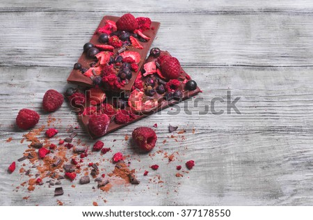 Handmade chocolate with fresh and dried berries, raspberries, strawberries, black currants, blackberries, cocoa powder, chips on light wooden background in rustic style, empty space for your text - stock photo