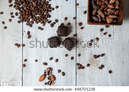 handmade chocolates without heat treatment lie on an old wooden table with cracked paint on the surface. raw food diet concept. Next to coffee and cocoa beans and grated cinnamon.Rustic style - stock photo