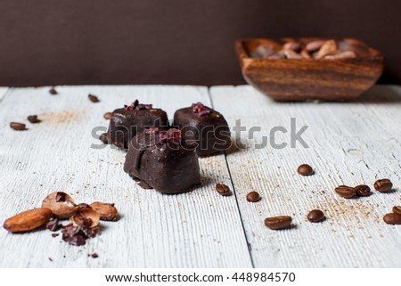 handmade chocolates without heat treatment lie on old wooden table with cracked paint the surface, wooden cup with cocoa beans. raw food diet concept.coffee cocoa beans grated cinnamon. rustic style - stock photo