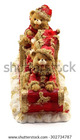 Handmade Christmas bears in sleigh in red and gold jackets and hats on snow isolated on white