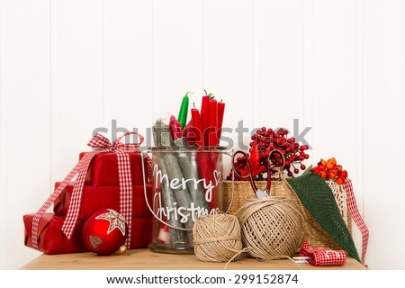 Handmade christmas boxes in red with creative utensils for decoration. - stock photo