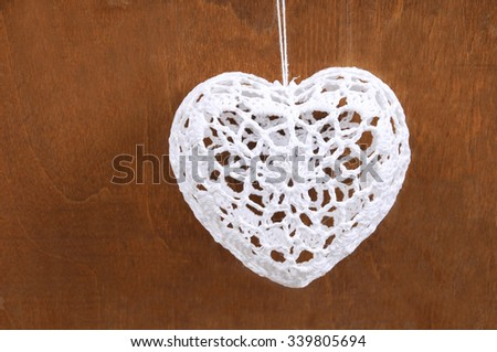 Handmade Christmas decoration. Heart hanging on wooden background. Vintage style, old wood background, with space for your text. Winter holidays concept - stock photo