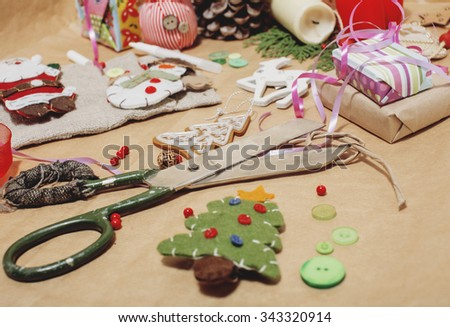handmade christmas gifts in mess with toys, candles, fir, ribbon wooden vintage - stock photo