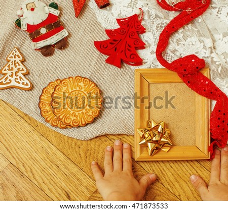 handmade christmas gifts in mess with toys, candles, fir, ribbon wooden vintage, buttons heart, kids hand holding empty frame