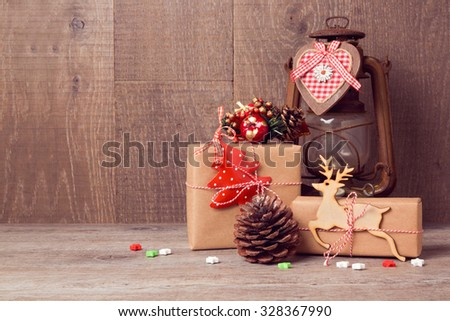 Handmade Christmas gifts with vintage lantern on wooden table - stock photo