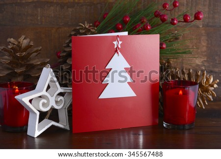 Handmade Christmas greeting card using cutout shapes on natural kraft paper on vintage wood table with festive decorations. - stock photo