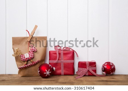 Handmade christmas presents wrapped in paper with red white checked ribbon and a hanging rocking horse. - stock photo