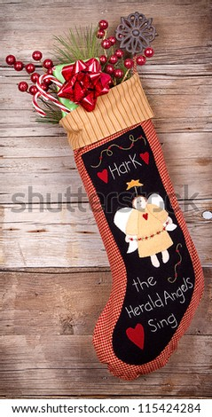 Handmade Christmas stocking stuffed with presents and decorations on wooden background