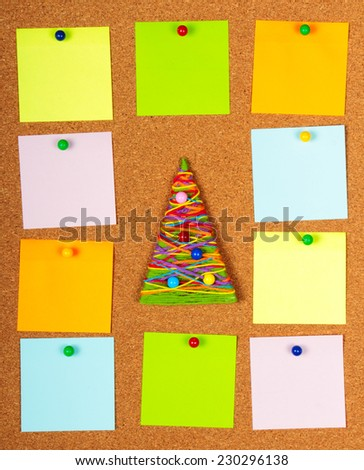 Handmade Christmas tree and empty note papers on cork board - stock photo
