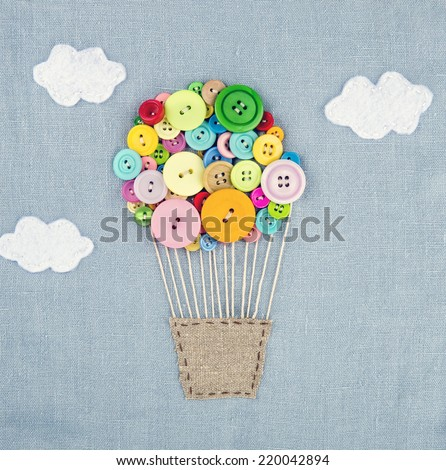 Handmade crafts of hot air balloon made of multicolored buttons on light blue linen textile background - stock photo